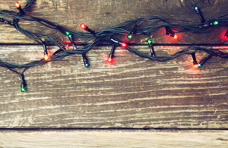 Colorful Christmas lights on wooden  rustic background. filtered image photo