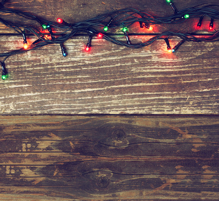 Colorful Christmas lights on wooden  rustic background. filtered image