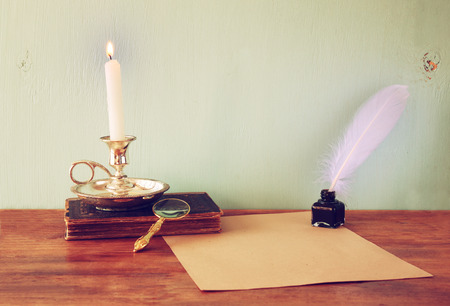 low key image of white Feather, inkwell, burning Candle and ancient book on wooden table.  filtered image photo