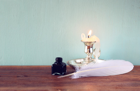 low key image of white Feather, inkwell, and candle on old wooden table photo