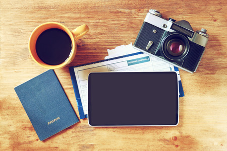 plane table: top view image of tablet with empty screen, old camera passport and flight boarding pass. Stock Photo