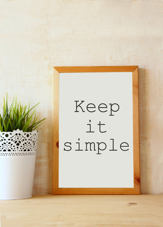 white drawing board with the phrase \ keep it simple\ written on it against textured wall photo