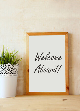 welcome desk: drawing board with the phrase welcome aboard handwritten over wooden table. Stock Photo
