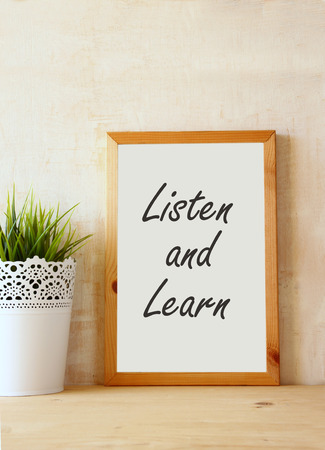 the phrase listen and learn written over white drawing board against rustic textured wall photo