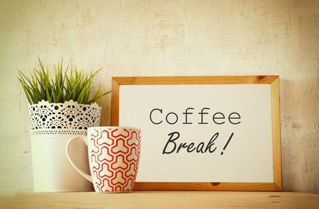 white drawing board with the phrase coffee break over wooden table with coffe cup and flower pot decoration . filtered image Stock Photo