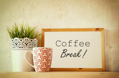 Weiß-Zeichnung Board mit dem Satz Kaffeepause über Holztisch mit Kaffeetasse und Blumentopf Dekoration. gefilterte Bild