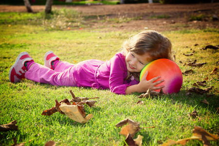 litle: Little lovely girl playing with her ball on the grass in the park. filtered image