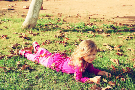 litle: Little lovely girl playing on the grass in the park. filtered image