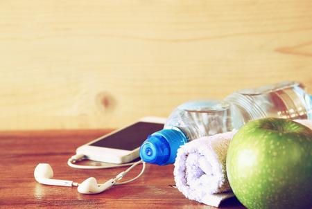Bas l'image clé du concept de remise en forme avec une bouteille d'eau, téléphone mobile avec des écouteurs, une serviette et de pomme sur fond de bois. image filtrée avec mise au point sélective Banque d'images - 33506383