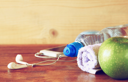 low key  image of fitness concept with bottle of water, mobile phone with earphones, towel and apple over wooden background. filtered image with selective focus photo