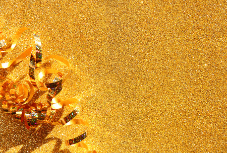 top view image of curly golden ribbon over textured glitter background photo