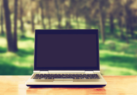 laptop outside: laptop with blank screen over wooden table outdoors and blurred background of trees in the forest Stock Photo