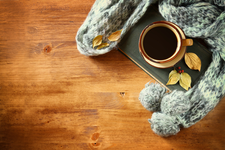 Top view of Cup of black coffee with autumn leaves, a warm scarf and old book on wooden background. filreted image Standard-Bild