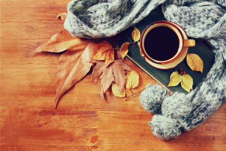 wooden table top view: Top view of Cup of black coffee with autumn leaves, a warm scarf and old book on wooden background. filreted image Stock Photo