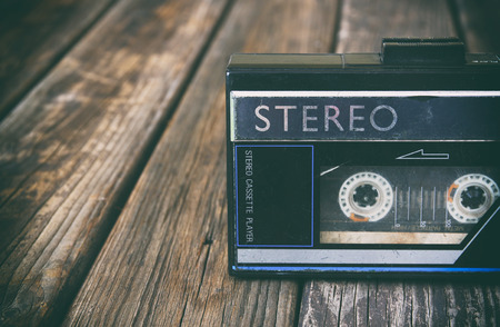 audio cassette: Old portable cassette player on a wooden background. image is instagram style filtered