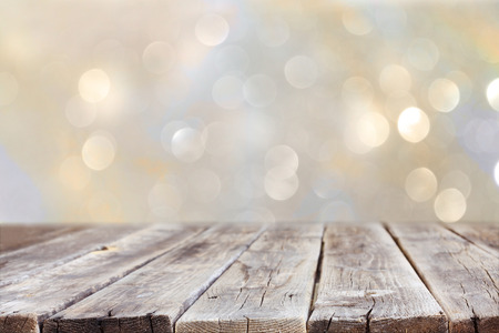 table: rustic wood table in front of glitter silver and gold bright bokeh lights