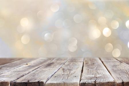tabulka: rustikální dřevěný stůl před lesk stříbra a zlata světlé bokeh světel