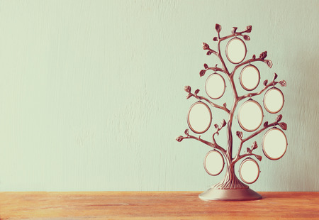 family memories: Image of vintage antique classical frame of family tree on wooden table Stock Photo