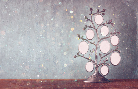 Image of vintage antique classical frame of family tree on wooden table and glitter lights background . filtered image Archivio Fotografico