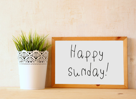 self study: the phrase happy sunday   written over white drawing board against rustic textured wall Stock Photo