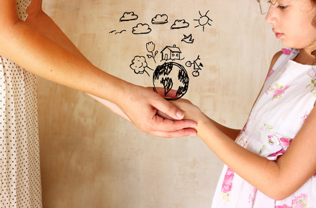 happy world: photo of mother and child holding hands and showing a better world concept with set infographics . protection and education concept Stock Photo