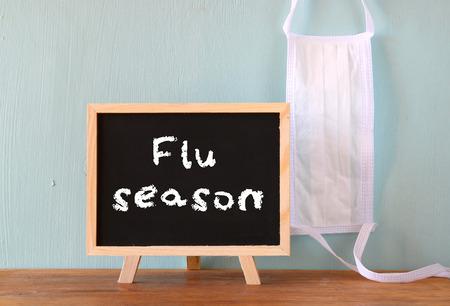 gripe: pizarra con la temporada de gripe frase escrita en �l y mascarilla