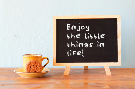 the next life: blackboard with the phrase enjoy the little things in life next to coffee cup over wooden table Stock Photo