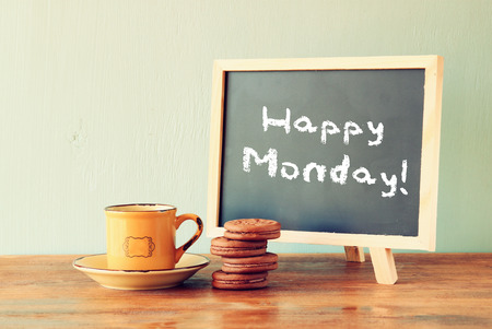 weekends: blackboard with the phrase happy monday next to cup of coffee and cookies