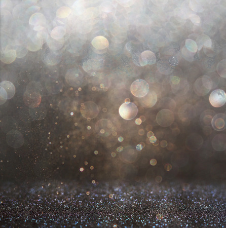 glitter vintage lights background. gold, silver, and black. de-focused.