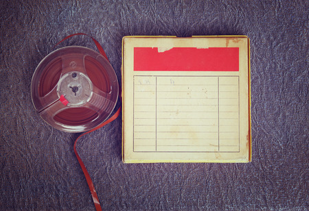top view of  old sound recording tape, reel to reel type and box with room for text. filtered image Stock Photo