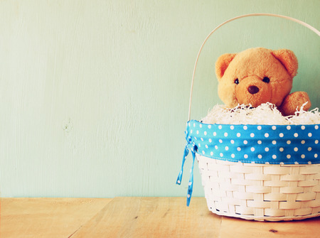 single shelf: toy teddy bear in basket on wooden table. retro filtered image Stock Photo