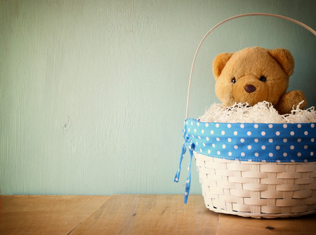 toy teddy bear in basket on wooden table. retro filtered image photo