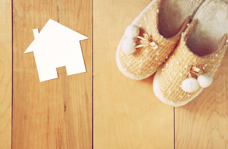 top view of warm woman slippers over wooden floor and paper house shape as welcome home concept