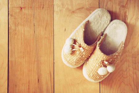 top view of warm woman slippers over wooden floor photo