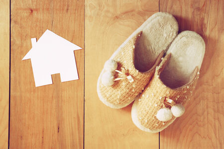 wooden shoes: top view of warm woman slippers over wooden floor and paper house shape as welcome home concept
