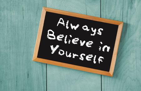 believe: vista desde arriba de la pizarra con la frase siempre creer en ti mismo, sobre fondo de madera