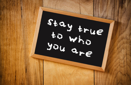 true self: top view of blackboard with the phrase stay true to who you are, over wooden background
