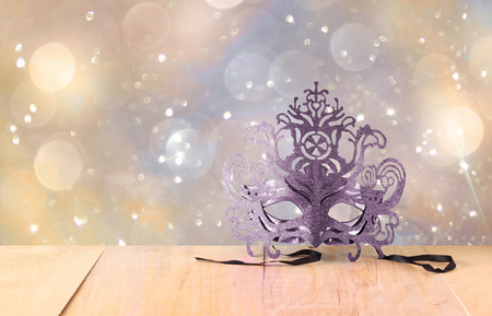 winter theater: Mysterious Venetian masquerade mask on wooden table and glitter background