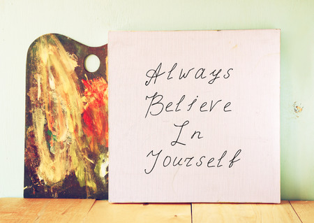canvas board with the phrase always believe in yourself, over wooden background photo