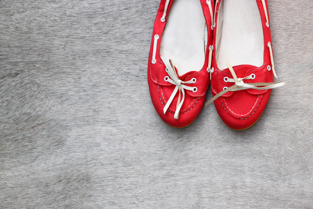 wooden shoes: top view of red worn woman shoes over wooden textured background.  Stock Photo