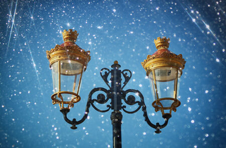 street lamp: Picture of an antique street lamp against night  sky. vintage filtered image and bokeh lights.