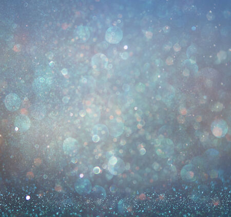 glitter vintage lights background with light burst . silver, blue and white. de-focused. photo