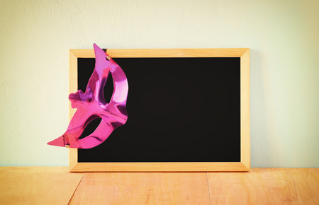 megillah: Mask and blackboard, room for text. filtered image Stock Photo