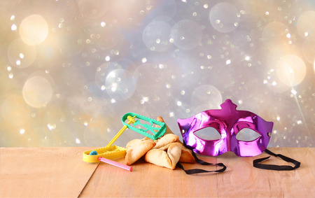 Hamantaschen cookies or hamans ears,noisemaker and mask for Purim celebration (jewish holiday) and glitter background