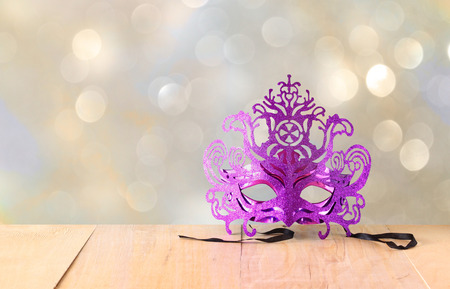 Mysterious Venetian masquerade mask on wooden table and glitter background photo