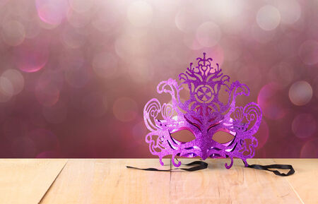 dust mask: Mysterious Venetian masquerade mask on wooden table and glitter background