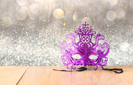 queen's theatre: Mysterious Venetian masquerade mask on wooden table and glitter background