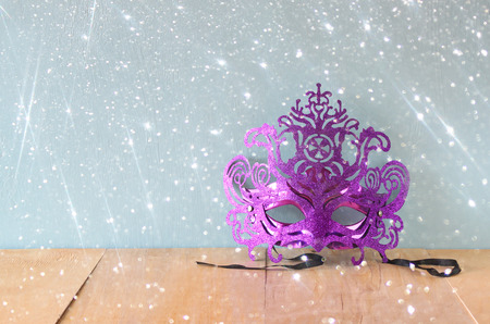 Mysterious Venetian masquerade mask on wooden table with glitter overlay photo
