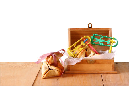 haman: Hamantaschen cookies or hamans ears and noisemaker for Purim celebration (jewish holiday) with isolated background