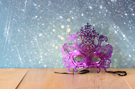 queen's theatre: Mysterious Venetian masquerade mask on wooden table with glitter overlay